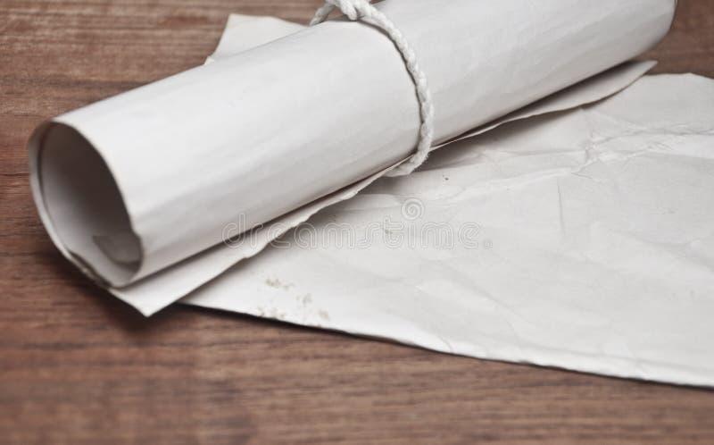 与纸的古老纸卷在木桌上 图库摄影