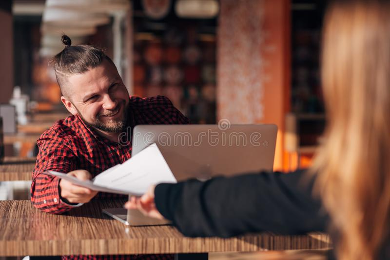 与纸的笑的商人谈话与她的同事在会议期间在咖啡馆 免版税库存照片
