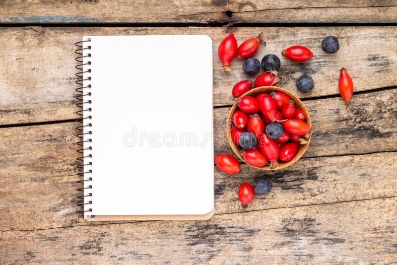 与纸笔记本的新鲜的野生莓果在木桌上 免版税库存照片