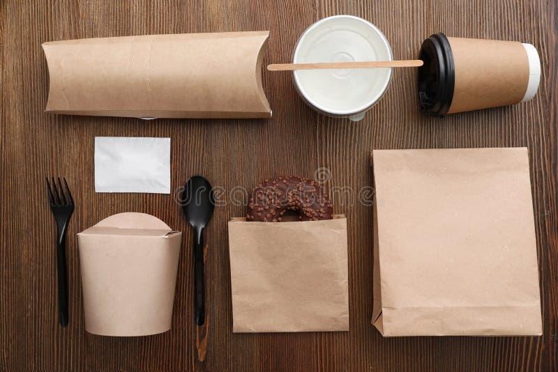 与纸袋和不同的外带的项目的平的被放置的构成在木背景 免版税库存照片