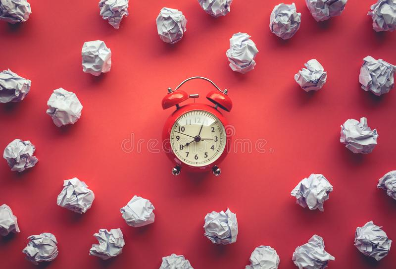 与纸被弄皱的球和闹钟的表现概念在工作台背景 时刻和发稿日期和地点 免版税库存图片
