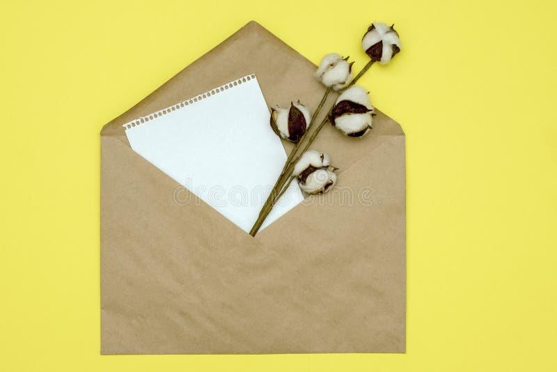 与纸页和棉花分支的纸信封从它的在黄色背景 与拷贝空间的大模型 免版税库存图片