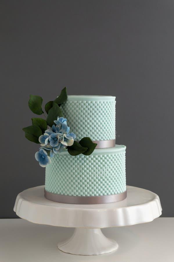 与纹理和可食的糖花的典雅的2排婚宴喜饼 库存图片