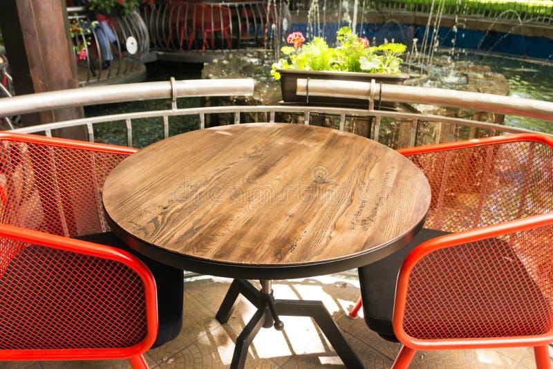 与纹理的一张空的木桌,在被弄脏的背景前面 与花、植物和喷泉的一个清淡的街道咖啡馆- 免版税图库摄影