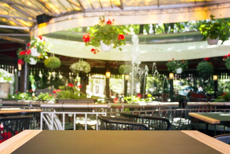 与纹理的一张空的木桌,在被弄脏的背景前面 与花、植物和喷泉的一个清淡的街道咖啡馆- 库存图片