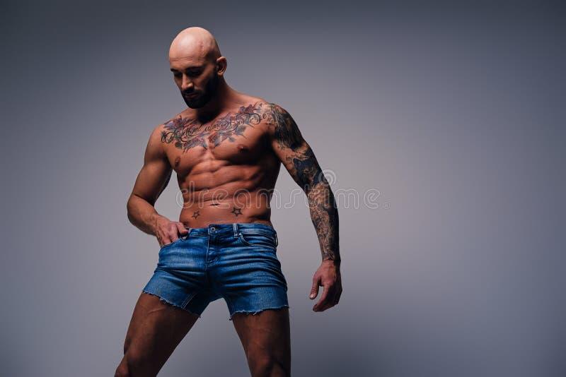 小s小象纹身_与纹身花刺的被刮的顶头,肌肉男性在他的在灰色v的躯干 库存 ...