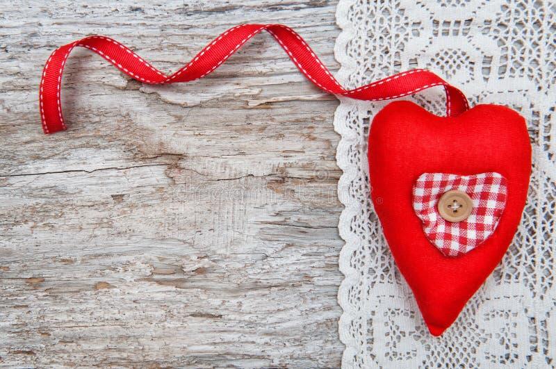 与纺织品心脏的华伦泰卡片在有花边的布料和老木头 免版税库存图片