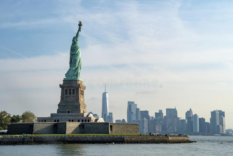 与纽约地平线的自由女神像在背景中 免版税图库摄影