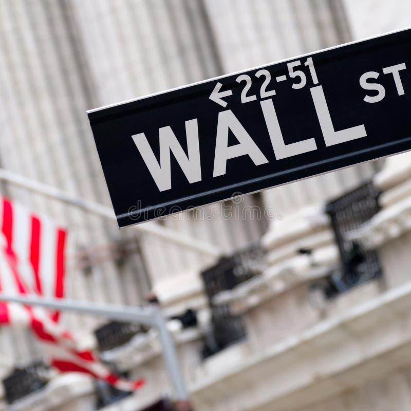 与纽约证券交易所的华尔街标志在backgro 免版税库存图片