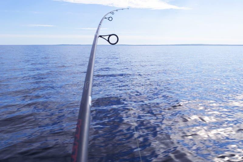 与线特写镜头的钓鱼竿转动的圆环 在水晶寂静的水的钓鱼竿 钓鱼竿圆环 r Fis 免版税图库摄影