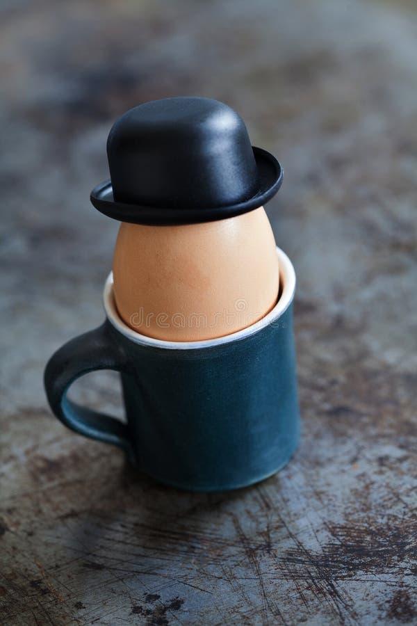 与绅士圆顶硬礼帽的Egg先生黑色 黏土杯子煮沸了红皮蛋,破旧的背景 创造性的食物概念 免版税图库摄影