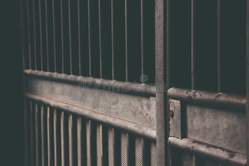 与细胞酒吧的老监狱被锁背景深黑色和轻 ?? 库存照片