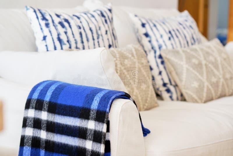 与织品材料白色颜色沙发蓝色米黄元素坐垫和格子花呢披肩关闭的客厅内部图象 库存照片