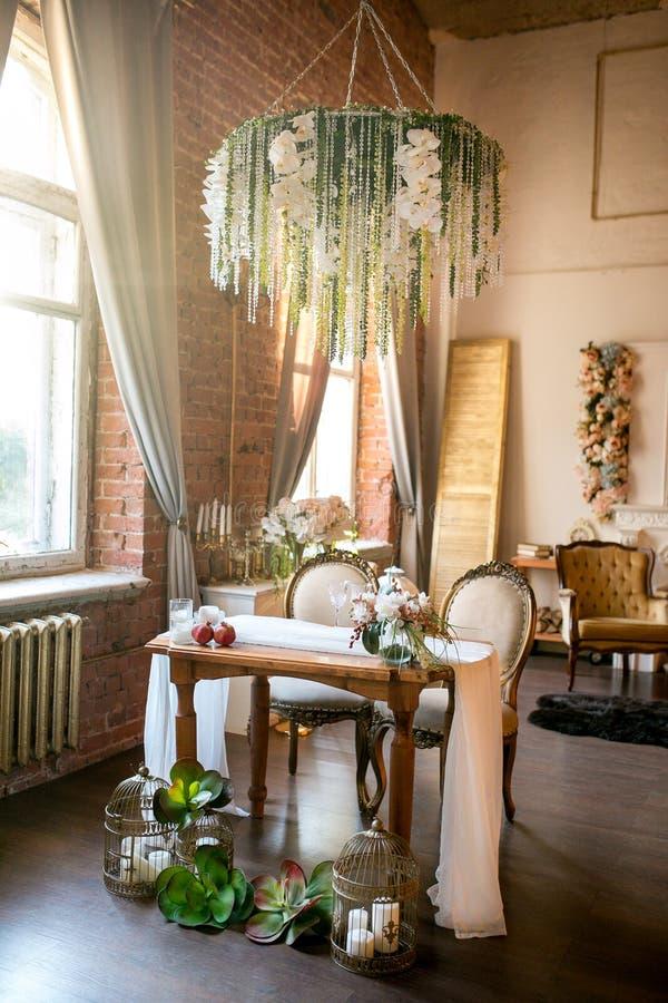 与经典椅子、花枝形吊灯、果子和多汁植物的餐桌在与花的顶楼空间 免版税库存照片