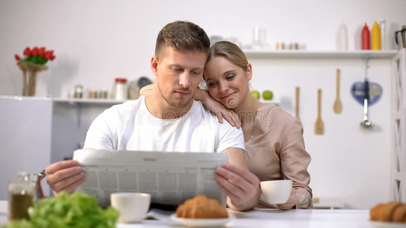 与结合在一起使咖啡杯,早晨的妻子的年轻丈夫读书报纸 免版税图库摄影