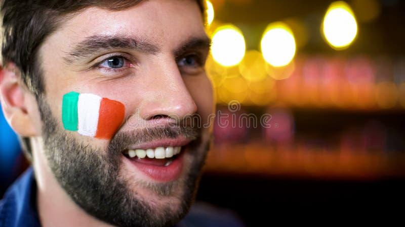 与绘的意大利爱好者在面颊旗子微笑的观看的体育竞赛 库存照片