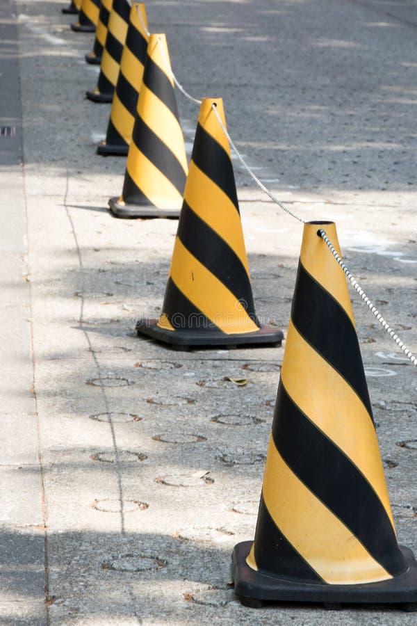 与绳索的黄色和黑颜色交通锥体对指南 免版税库存图片