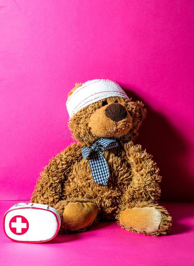 与绷带和急救的玩具熊的不幸事故概念 库存图片