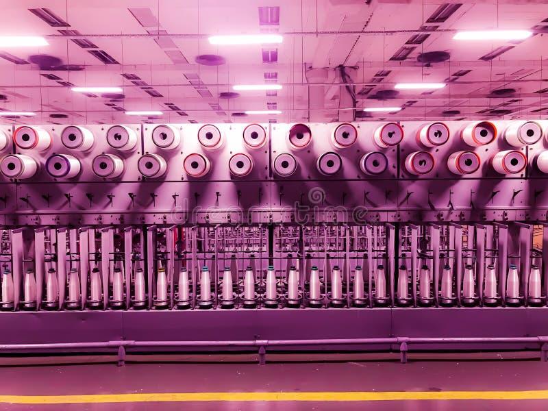 与综合性螺纹的卷轴 与玻璃纤维的卷 玻璃纤维制造  玻璃纤维的生产的工厂 库存照片