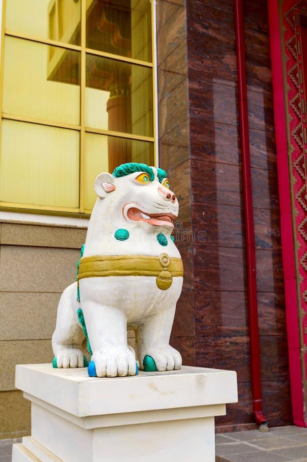 与绿松石鬃毛的西藏雪狮子在对佛教寺庙的入口前面 雪喜马拉雅山和天空的标志 库存照片