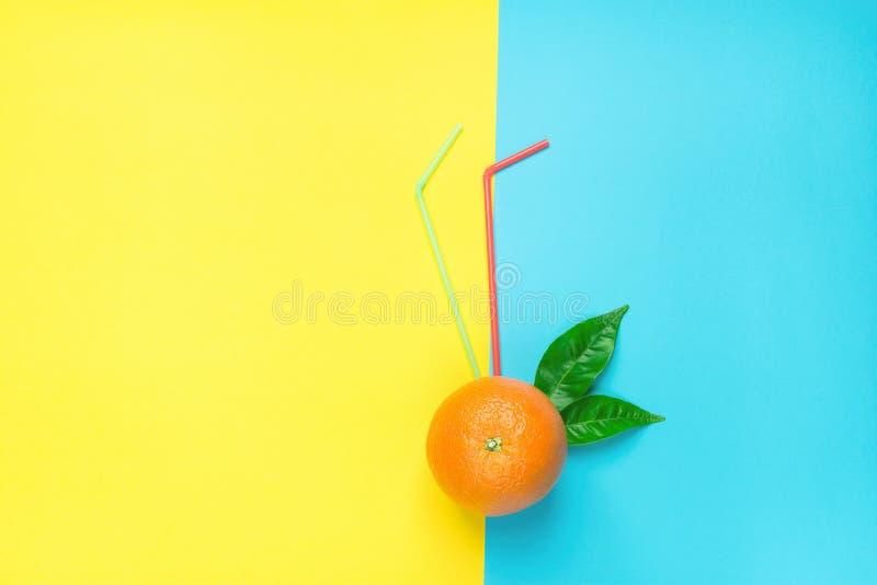 与绿色叶子吸管的成熟水多的整个桔子在Duotone黄色蓝色背景 新鲜的汁液夏天鸡尾酒 库存图片