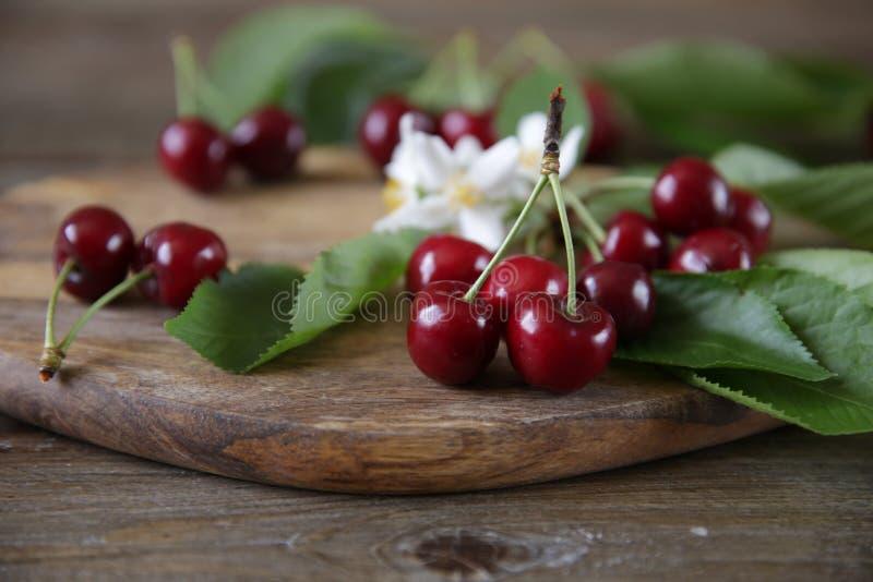与绿色叶子和白花的新鲜的有机甜樱桃在木土气背景 r r 免版税库存图片