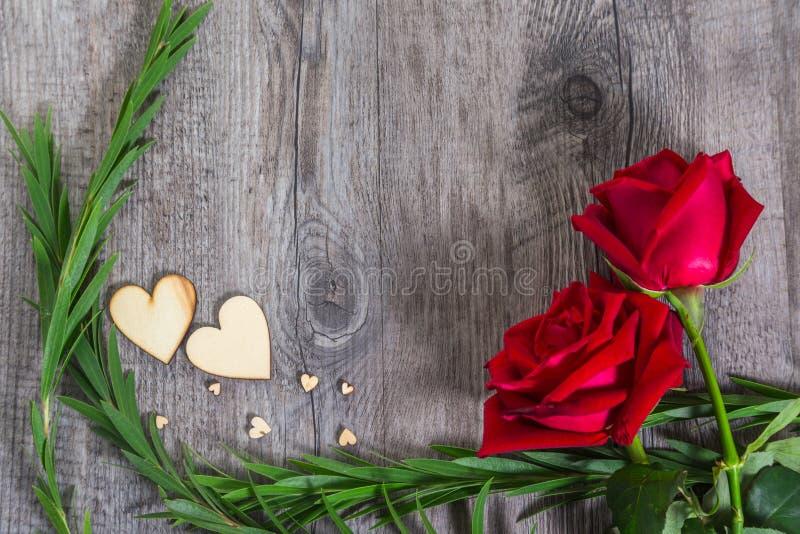 与绿色叶子和红色玫瑰的心脏形状在木纹理背景开花 免版税库存照片