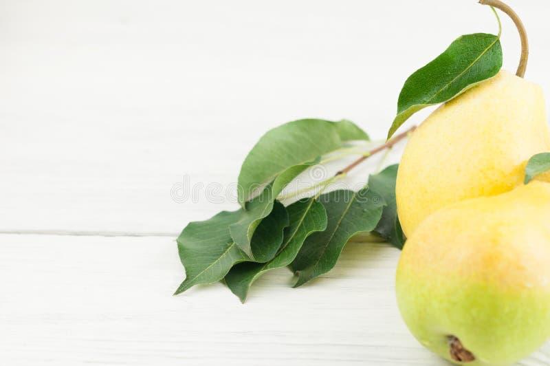 与绿色叶子的两个新鲜的整个成熟梨 免版税库存图片