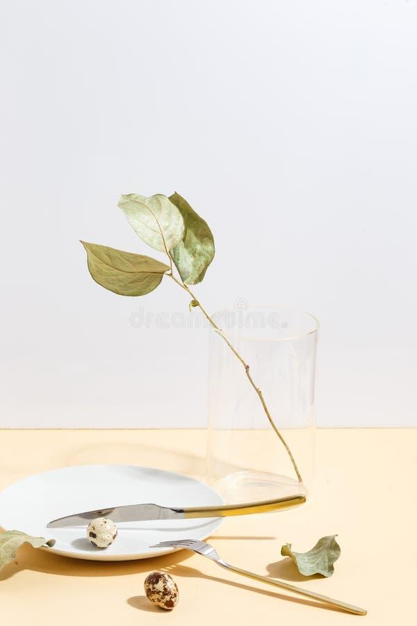 与绿色叶子的干燥分支在一个玻璃花瓶 白色板材和镀金的利器在米黄背景 免版税图库摄影