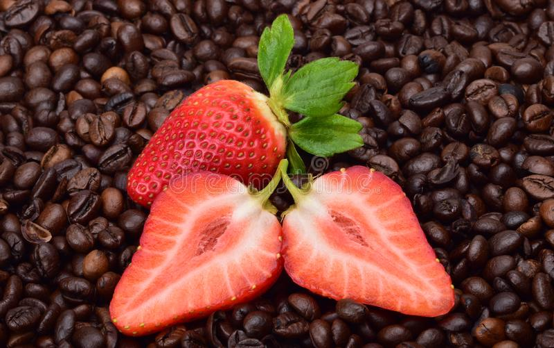 与绿色叶子的成熟夏天草莓以烤芬芳咖啡为背景 库存图片