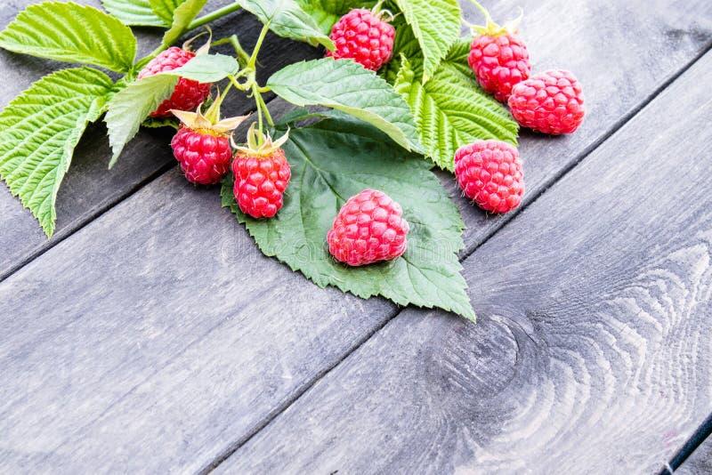 与绿色叶子的成熟红草莓在老黑暗的委员会背景  r 图库摄影