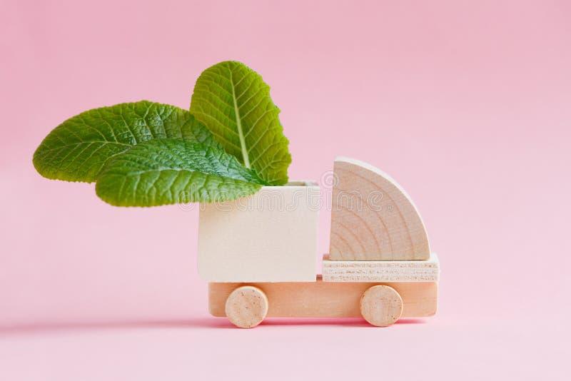 与绿色叶子的玩具木货物卡车模型 免版税库存照片