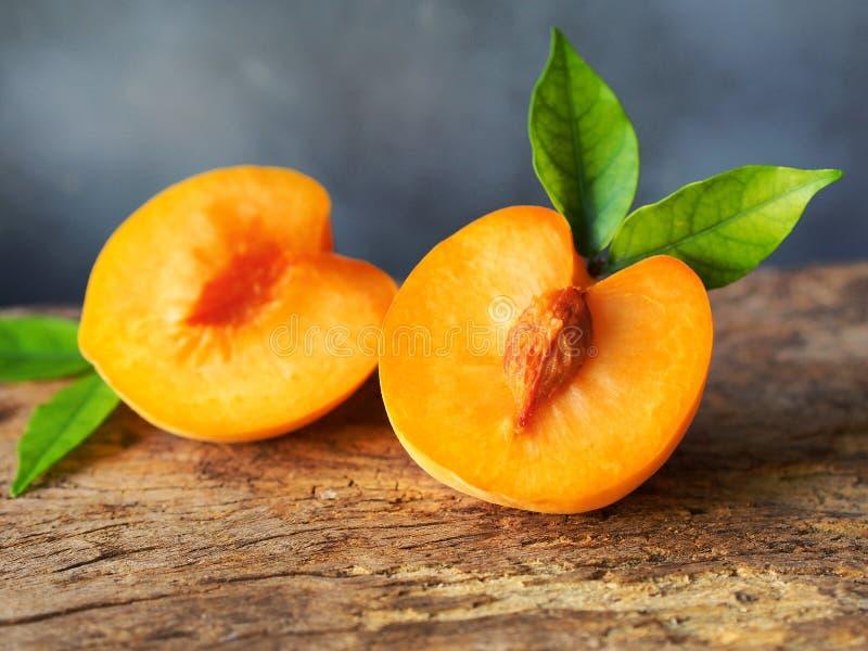 与绿色叶子的金黄水多的桃子 免版税库存照片