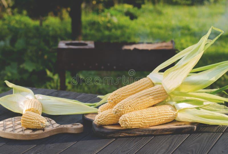 与绿色叶子的黄色水多的玉米在一张木桌上说谎在夏天庭院里反对格栅的背景 免版税库存图片