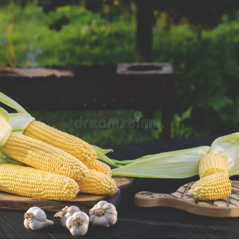 与绿色叶子的黄色水多的玉米在一张木桌上说谎在夏天庭院里反对格栅的背景 库存图片