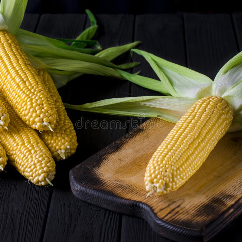 与绿色叶子的黄色水多的玉米在一张黑树桌上 免版税库存图片