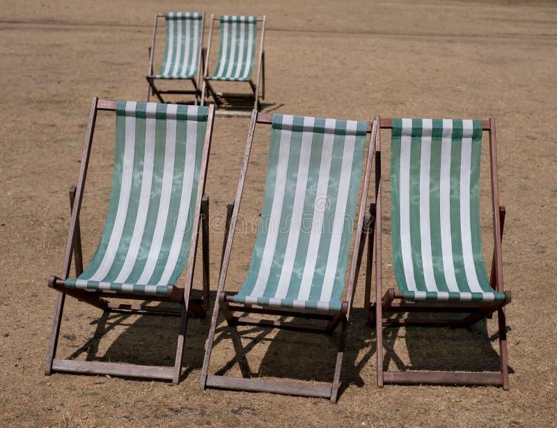 与绿色和白色条纹的轻便折叠躺椅在死的草在海德公园,在夏天热浪期间的伦敦, 2018年7月 库存照片