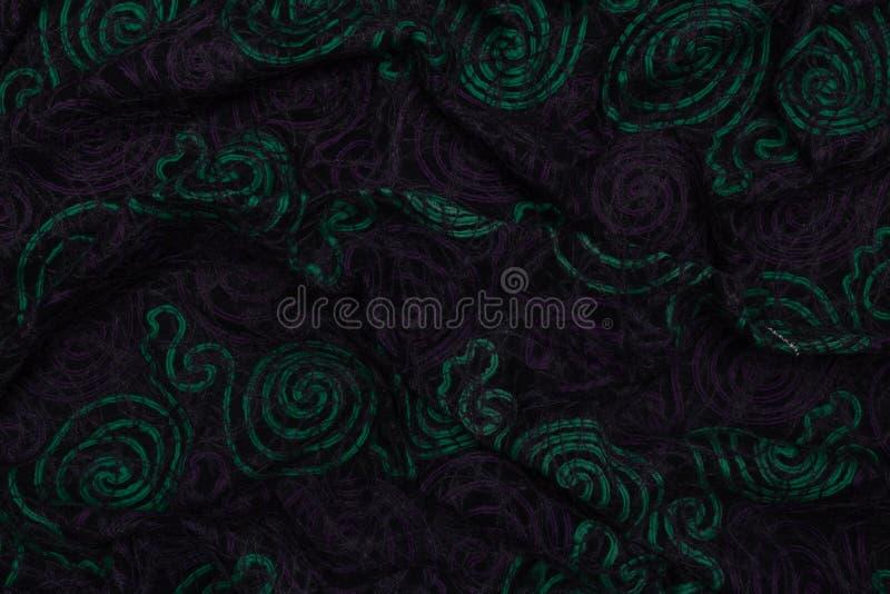 与绿色和紫罗兰色样式的创造性的黑暗的织品有纺织品纹理背景 库存图片