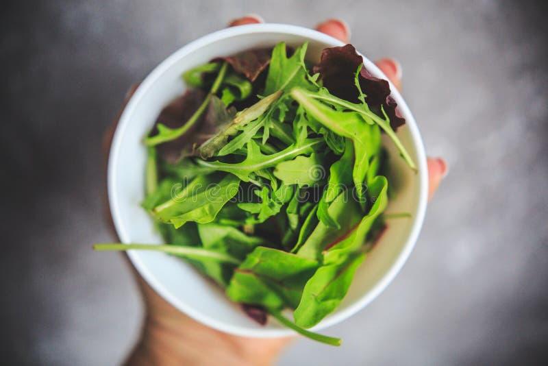 与绿色和紫色水多的颜色的新鲜的凉拌生菜在从上面采取的浅灰色的背景的白色碗 免版税库存照片