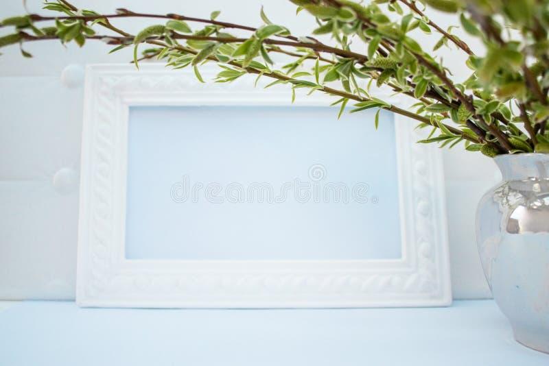 与绿色杨柳分支的白色框架在蓝色背景的 E 免版税库存照片