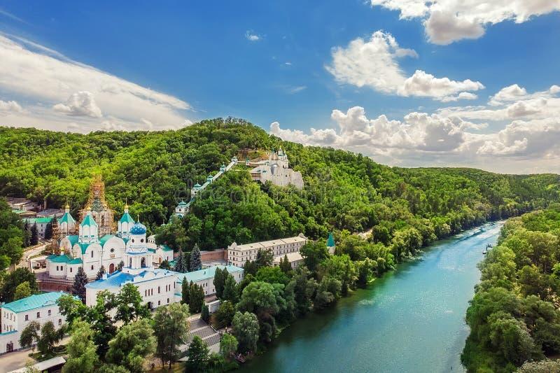 与绿色森林和顿涅茨河的Svaytogorsk lavra古老修道院小山全景Donbass的,明亮晴朗的乌克兰 库存照片