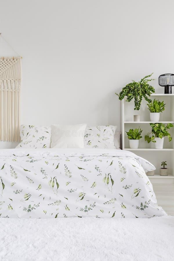 与绿色植物样式的斯堪的纳维亚样式卧室内部在躺在床上的白色卧具 在地板上的蓬松地毯 空的墙壁 免版税库存照片