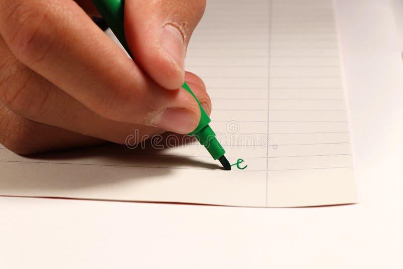 与绿色毡尖的笔的年轻男孩文字在英国教训的某一词在小学 免版税库存照片