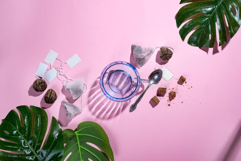 与绿色热带叶子和茶杯的工作区框架,茶包和糖在粉红彩笔背景与深阴影 图库摄影