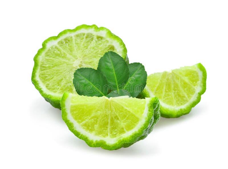 与绿色的切的新鲜的香柠檬在白色离开 库存图片
