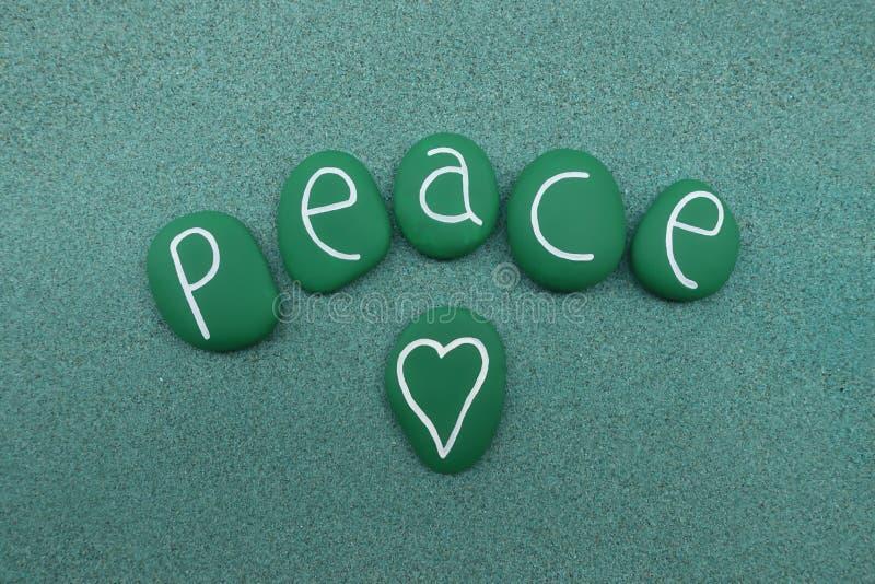 与绿色的和平词绘了在绿色沙子的海石头 免版税图库摄影