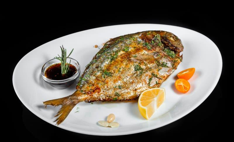 与绿色的烤dorado在被隔绝的黑背景的鱼和柠檬 免版税库存照片