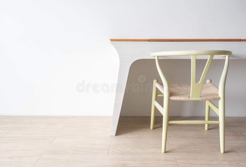 与绿色经典椅子和现代桌的最低纲领派建筑师设计师概念在木地板上有白色墙壁背景 图库摄影