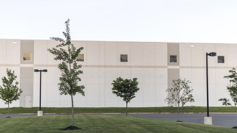 与绿色草坪和街灯的普通仓库办公全套设备Buildilng 库存照片