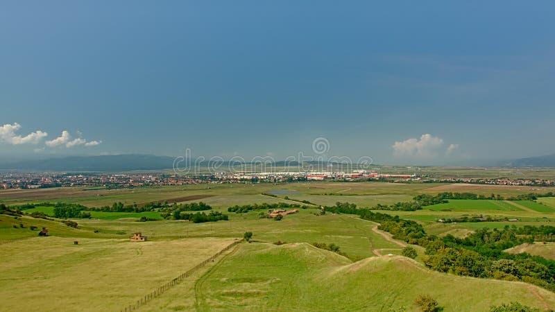与绿色草甸的Transylvanian风景和城市和山在背景中 免版税库存照片